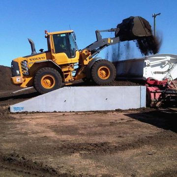 dozer using loading ramps to pour sand on truck