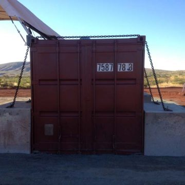 container tied by concrete tie down blocks