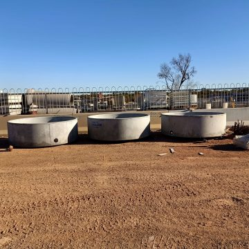 three concrete round cattle water trough in a row