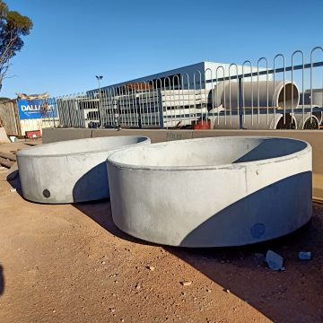 two concrete round cattle water trough
