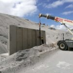 crane installing retaining wall