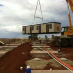 mobile crane lifting shed on construction site